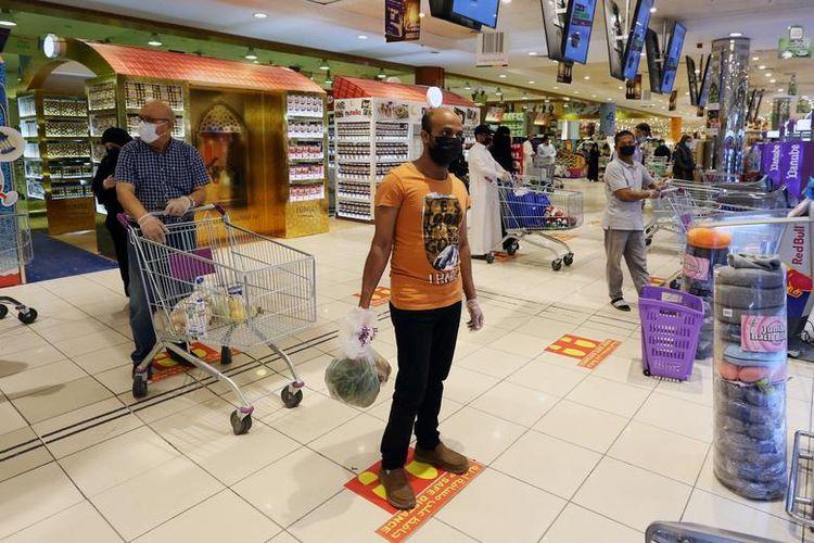 Люди дотримуються позначок соціальної дистанції, коли вони чекають у черзі в торговому центрі в Ер-Ріяді, Саудівська Аравія