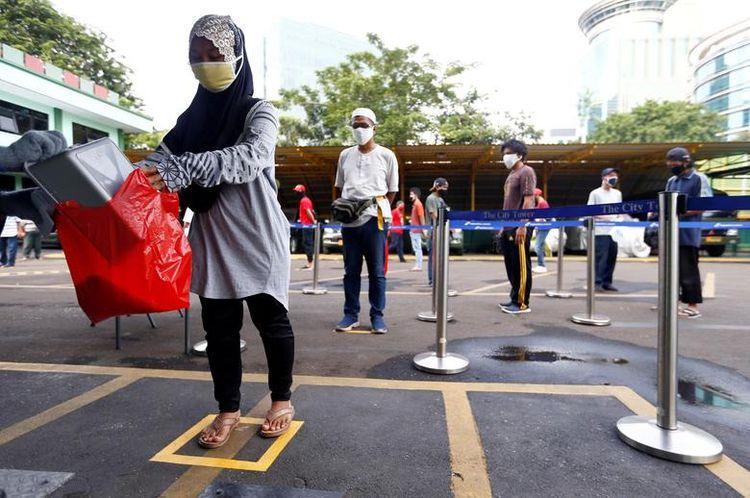 Люди практикують соціальне дистанціювання, отримуючи рис від автоматизованого розповсюджувача рисових банкоматів в Джакарті, Індонезія