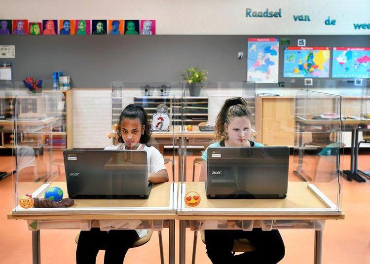 Учні сидять за дошками перегородки з оргскла, відвідуючи заняття в початковій школі в Den Bosch, Нідерланди