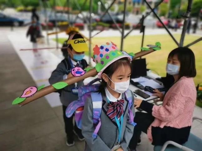 У Китаї діти прийшли до школи в метрових капелюхах, щоб тримати відстань
