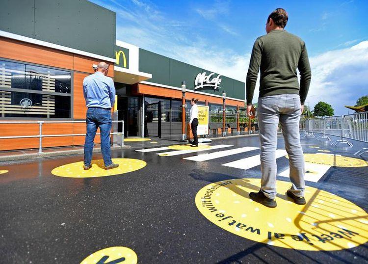 Клієнти чекають на вулиці, стоячи на маркованих відрізках соціального дистанціювання перед будівлею McDonald's в Арнем, Нідерланди