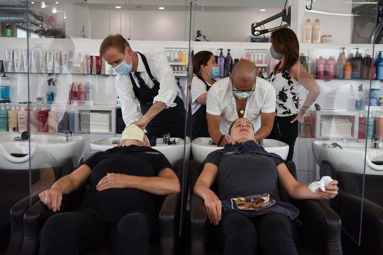 Жінки, розділені перегородками, миють волосся у перукарні після настанов щодо соціальної дистанції у Беллі Рінової в Х'юстоні, Техас, США