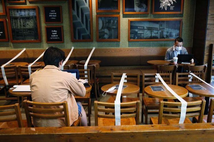 Столи та стільці перекриті для підтримання соціальної дистанції у кав'ярні Starbucks у Гонконзі