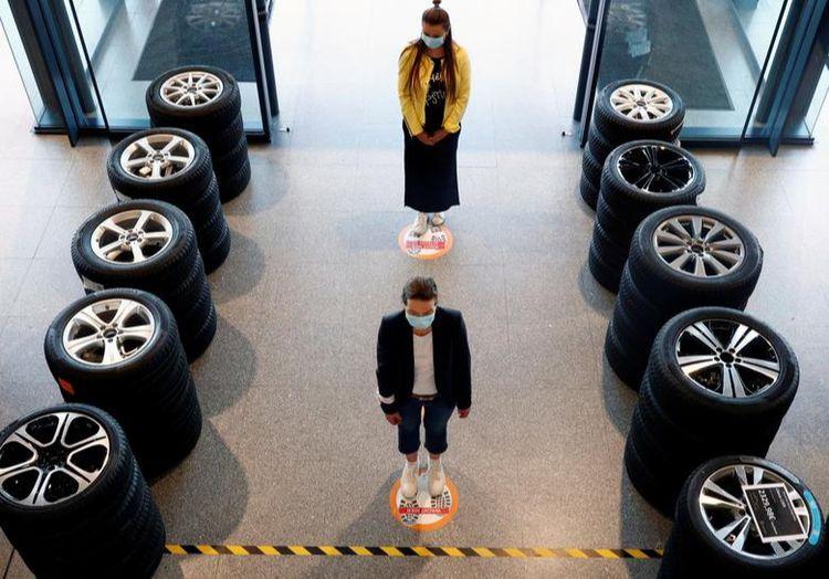 Люди стоять на маркерах соціального дистанціювання у дилера автомобілів Mercedes в Брюсселі, Бельгія