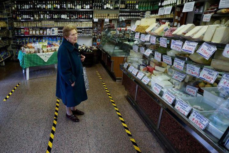 Леді чекає за жовтими лініями, що позначають відстань, яку клієнти повинні дотримуватися один від одного, в Римі, Італія
