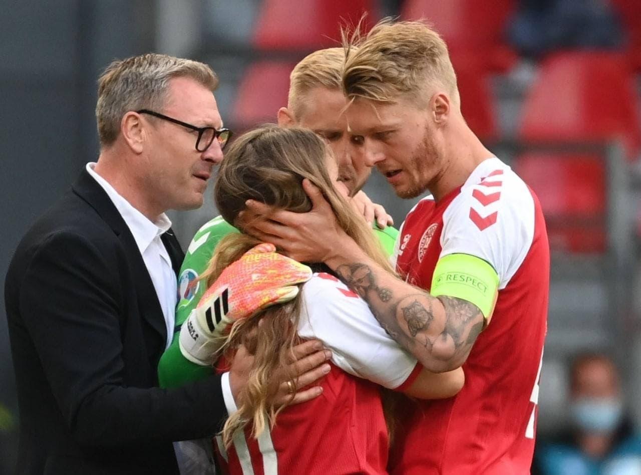 Гравці збірної Данії намагаються заспокоїти дружину Крістіана Еріксена Сабріну Квіст Єнсен, яка вибігла на поле...